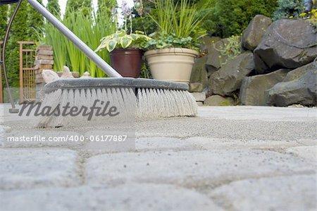 Broom Sweeping Locking Sand Into Backyard Patio Pavers Low View