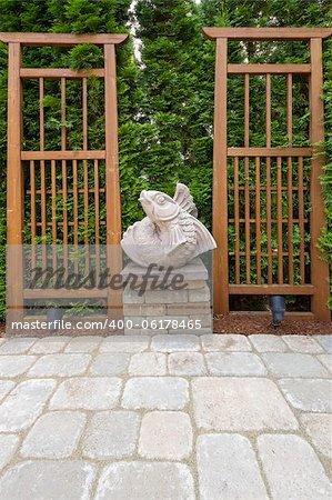 Asian Koi Fish Stone Sculpture in Garden Backyard Paver Patio with Trellis Background