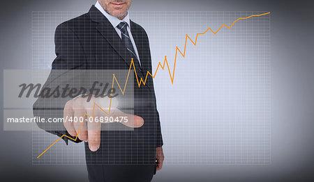 Businessman touching an orange curve on grey background