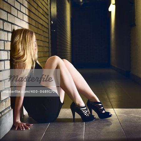 beautiful blond girl sitting on corridor floor