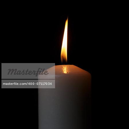 one burning candle, isolated on black background