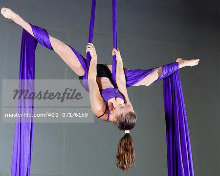 Beautiful woman gymnast performing aerial exercises