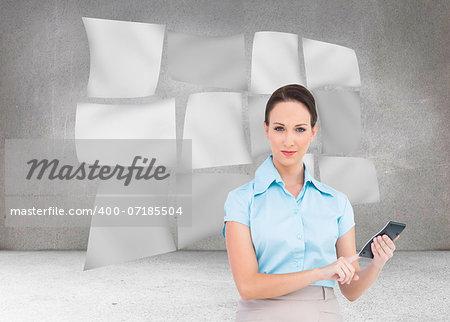 Composite image of serious classy businesswoman using calculator