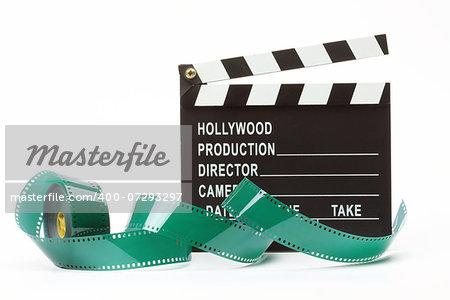 Movie clapper board and film roll over white