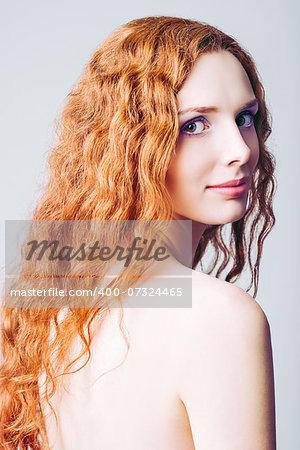 Closeup half-turned portrait of a beautiful smiling redhead girl