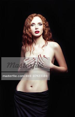 Dramatic studio portrait of a sexy redhead girl