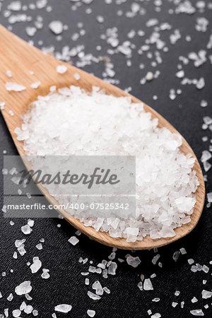 Sea salt in wooden spoon on a black table