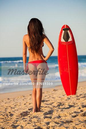 Girl in bikini with her surfboard looking to the sea