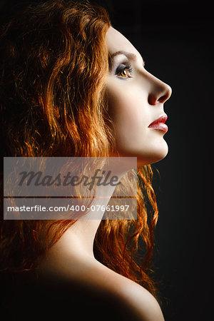 Closeup studio portrait of a beautiful redhead woman. Profile view