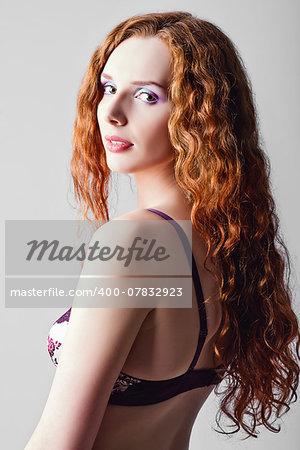 Closeup studio portrait of attractive ginger woman. Half-turned, high key