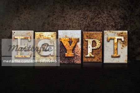 "The word ""EGYPT"" written in rusty metal letterpress type on a dark textured grunge background."