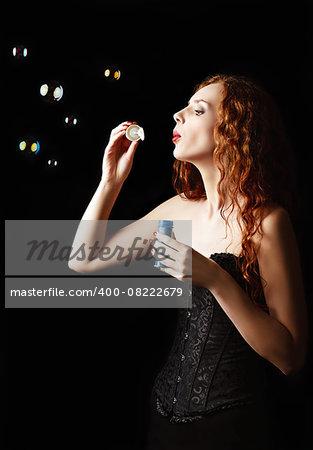 A beautiful redhead girl blows bubbles. Studio portrait, profile view