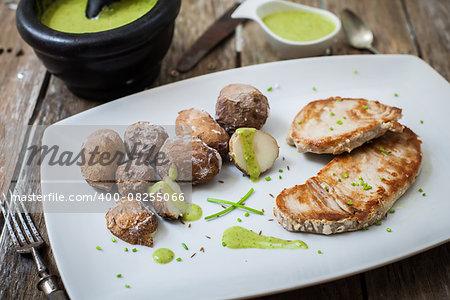 tuna steak with pesto sauce served with potatoes