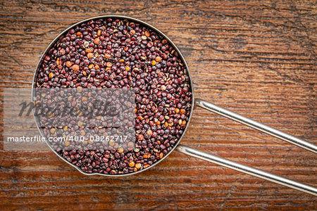 healthy, gluten free, black quinoa grain in a metal measuring cup against rustic wood