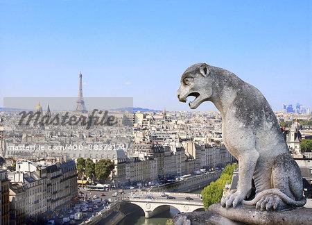 Gargoyle overlooking Paris up on Notre Dame de Paris and river Seine, France