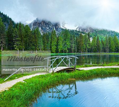 Beautiful summer Alpine  lake lago di Antorno view with sunshine through cloudy sky (Italia Dolomites)