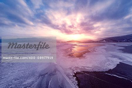 Frozen surface of Baikal lake at sunset. Russia.