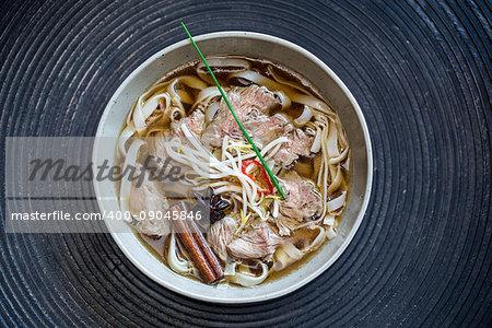 Pho bo beef noodle soup over dark background