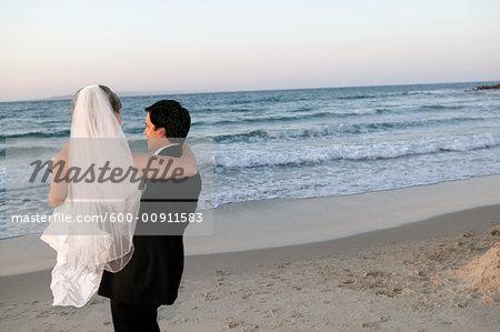 Groom Carrying Bride on Beach, Noosa Beach, Australia