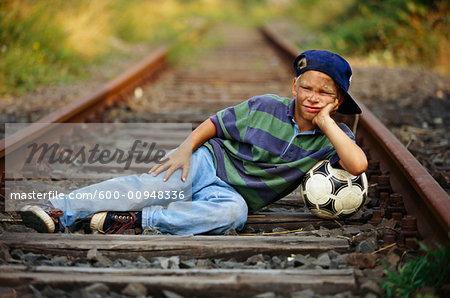 Boy With Soccer Ball Lying Down In Train Tracks