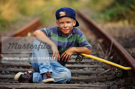 Boy With Skateboard Sitting On Train Tracks
