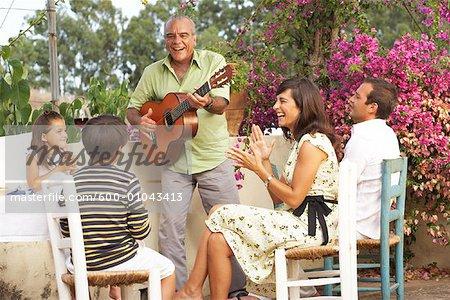 Family Sitting Outdoors Enjoying Man Playing Guitar