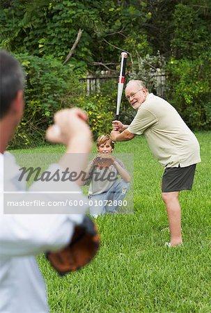 Family Playing Baseball in Backyard