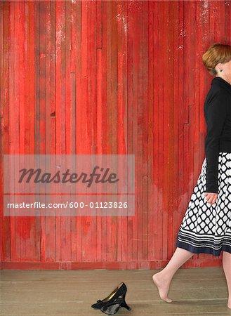Woman Walking Away from High Heel Shoes