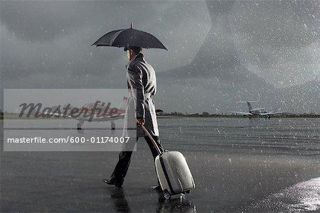 Businessman Walking on Tarmac in Rainy Weather
