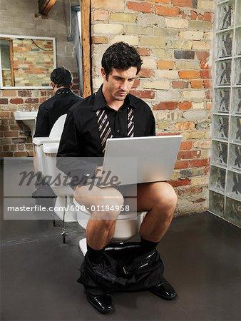 Man Sitting on Toilet Using Laptop Computer