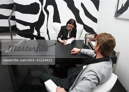 Businesswoman Sitting with Businessman at Desk