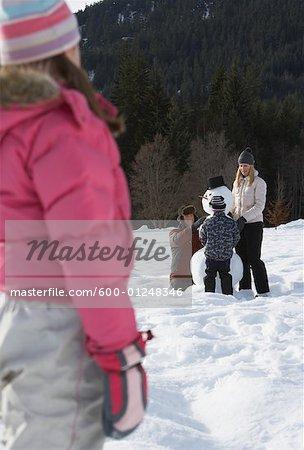 Girl Watching Family Make a Snowman