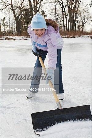 Girl Shoveling Snow from Rink