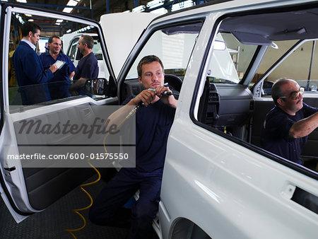 Men Working on Car in Factory
