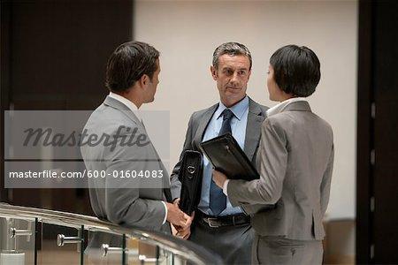 Business People Standing in Hallway Talking