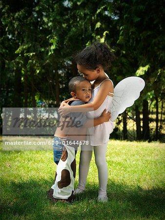 Girl and Boy Hugging in Yard