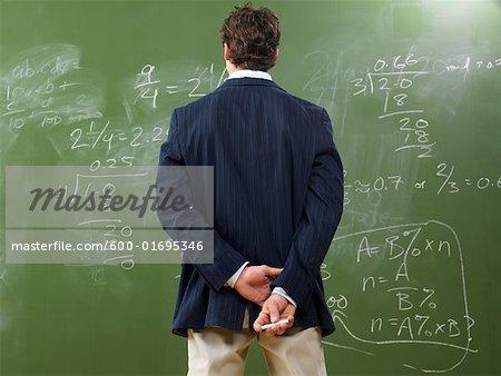 Teacher Looking at Math Problems on Blackboard