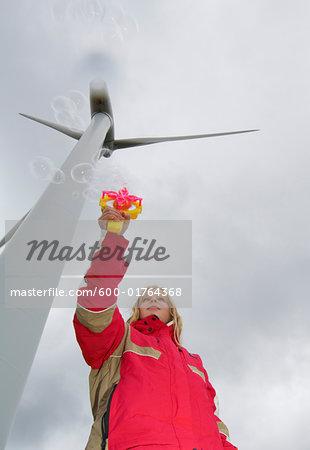 Girl Blowing Bubbles by Wind Turbine, Denmark