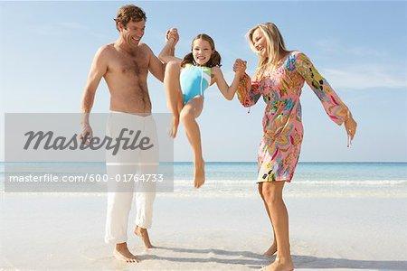Parents Lifting up Daughter on Beach, Majorca, Spain