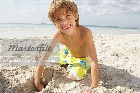 Boy Digging in Sand on Beach, Majorca, Spain