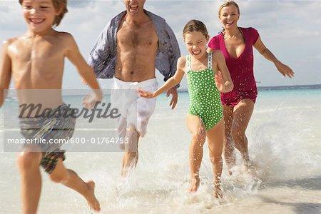 Family Running along Beach, Majorca, Spain