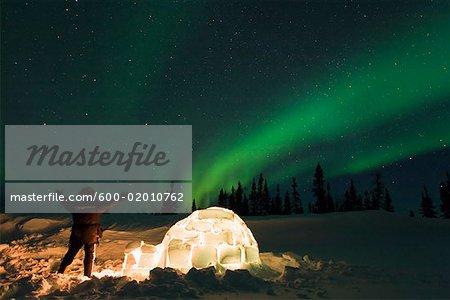 Person Standing near Igloo, Looking at Northern Lights, Wapusk National Park, Manitoba, Canada