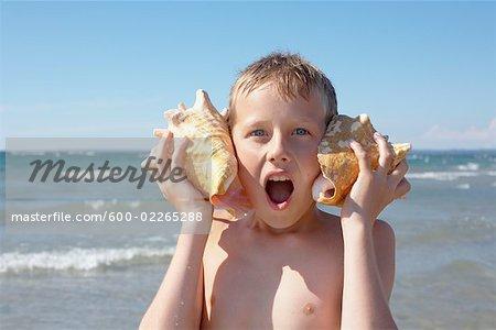 Boy Holding Seashells to His Ears, Elmvale, Ontario, Canada
