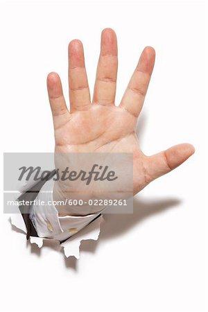 Businessman's Hand Bursting Through a Wall