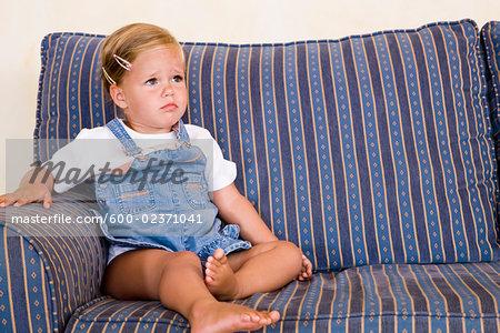 Girl Pouting on Sofa