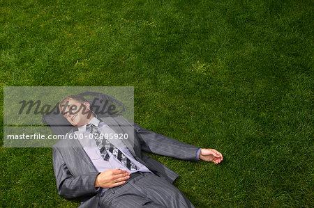 Businessman Lying on Grass Listening to Music