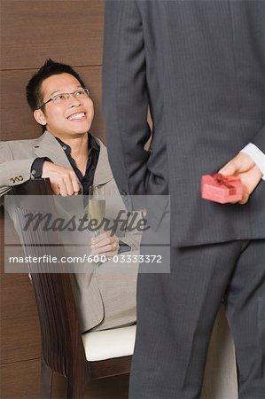 Man Holding Gift for Partner Behind Back