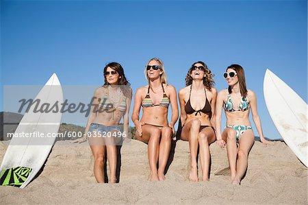 Young Women with Surfboards Sitting on Beach, Zuma Beach, California, USA
