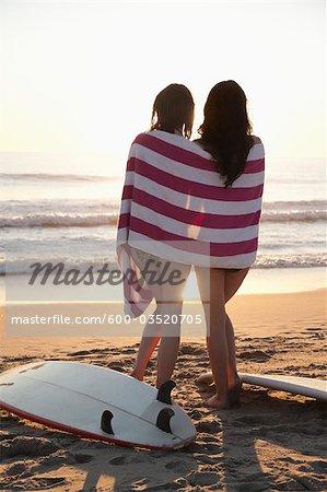 Backview of Young Women with Surfboards, Standing on Beach watching Sunset, Zuma Beach, California, USA