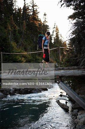 Woman Hiking Across Bridge, Garibaldi Provincial Park, British Columbia, Canada